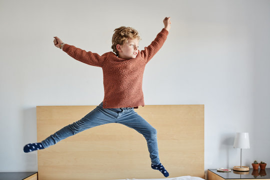 Little man jumping on the bed with energy