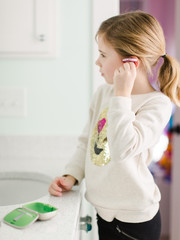 Young girl taking putting her hearing aids on