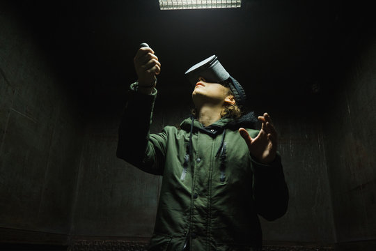 Young man using gray VR goggles finding himself in an industrial elevator