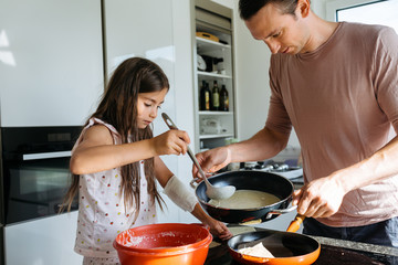 Father and little daughter cooking pancakes