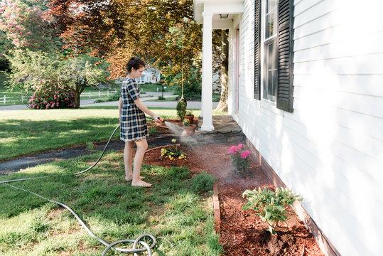 teen girl watering the flowers.