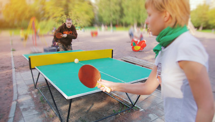 Group of happy young friends, girl and boy, playing ping pong table tennis with ball outdoors. Concept of healthy sport and genuine emotions. Active lifestyle, fun rest. Two people or player game.