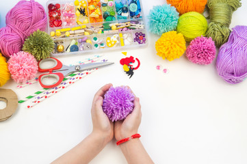 The child is engaged in a favorite hobby. The kid makes a pom-pom from a woolen thread monster. Holiday toy gift.