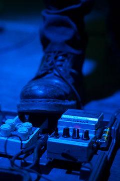 Rocker's boot on guitar pedals in blue light, vertical