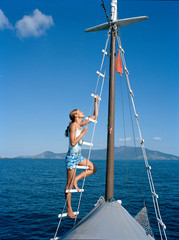 Young woman climbing ladder on sailboat