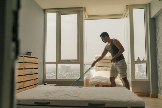 Asian man is cleaning his bedroom with warm summer light.