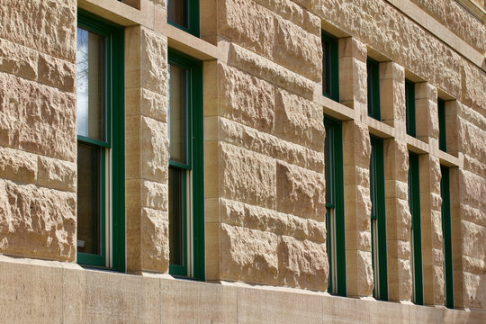 Exterior architectural stone wall of a 19th Century limestone building with modern window replacements