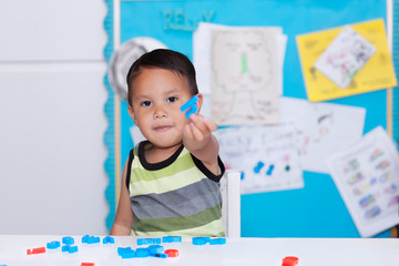 Smart boy giving or showing an alphabet letter in hand, sitting in a classroom learning how to spell words and demonstrating what he has learned.