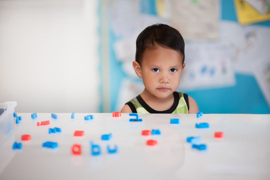 Young boy having difficulty learning in a kindergarten room with alphabet letters on the desk.