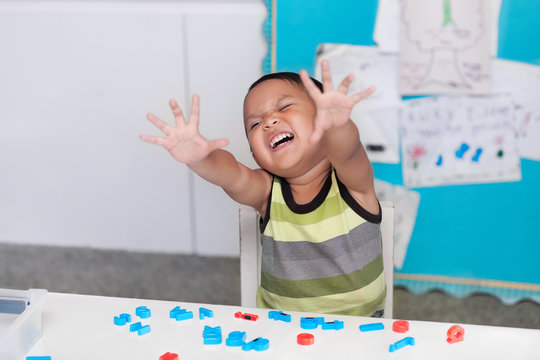 Hispanic young boy expressing disruptive or disorderly behavior in a classroom with alphabet letter manipulatives on the desk.