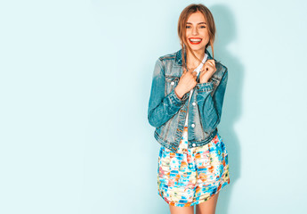 Portrait of young beautiful smiling hipster girl in trendy summer jeans jacket clothes. Sexy carefree woman posing near blue wall. Positive model having fun Wall mural