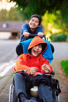 Sister pushing disabled little brother in wheelchair around neighborhood
