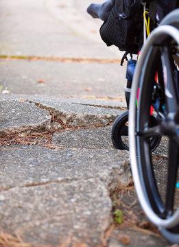 Wheelchair wheels up against cracks in broken sidewalk