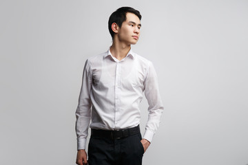 A young Asian man in a white shirt put one hand in his pants pocket, isolated on a gray background.