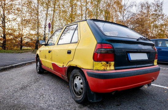 Old rusty car with colourful bodywork panels and neglected maintenance