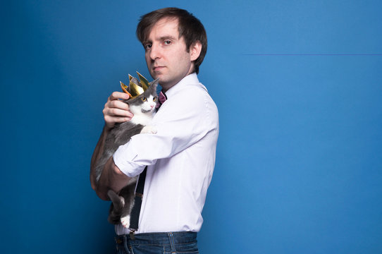 side view of handsome man in shirt and black suspenders looking at camera, holding and stroking grey cat in golden crown on blue background with copy space