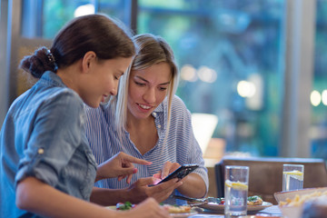 Side view of two smiling female friends browsing pictures on smart phone while having dinner at table in restaurant