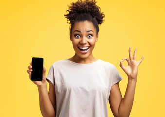 Overjoyed happy girl holds mobile phone and makes okay gesture. Photo of african american girl wears casual outfit on yellow background. Emotions and pleasant feelings concept.