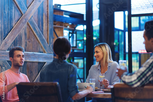 Four friends sitting at wooden table in restaurant and
