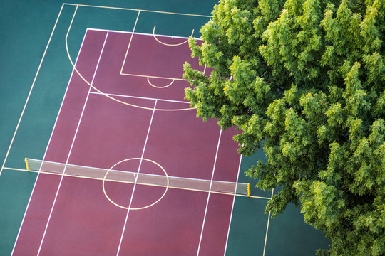 Universal sport court with on red ground background, top view in summertime.