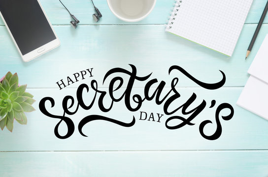 Desk with pencil, paper, cup, phone, headphones, notebook and succulent. Hand written lettering Happy Secretary's day
