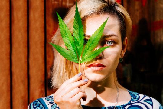 A girl with a cannabis leaf near her face