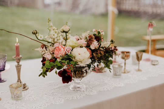 Burgundy, pink and white flowers centerpiece, white lace table linen, burning candles. Elegant wedding, event, dine dinning decor in marquee, outdoor.