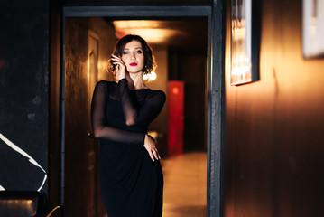 portrait of a beautiful brunette girl in a black dress in a dark room 1