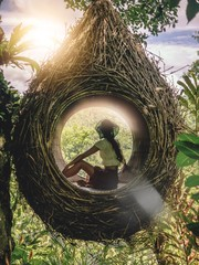 The girl in a giant nest looks at the jungle. Ecology, eco housing, harmony