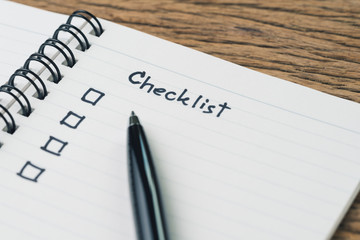 Checklist, to do list, prioritize or reminder for project plan, handwriting headline the word Checklist with black marker pen and check box on small notepad on wood table