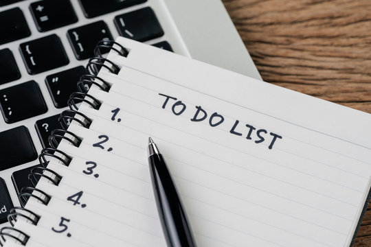To do list, checklist of things or tasks to complete for life habit, business project plan concept, black pen on notepad with headline To do list and list of numbers on computer laptop, wooden table
