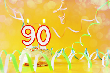 Ninety years birthday. Cupcake with burning candles in the form of number 90. Bright yellow background with copy space