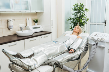 Blonde girl lying on beauty couch during pressotherapy session in clinic