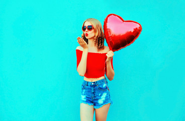 Portrait beautiful young woman sending sweet air kiss with red heart shaped balloon on colorful blue background