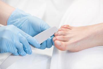 Process of pedicure of female legs at beauty salon