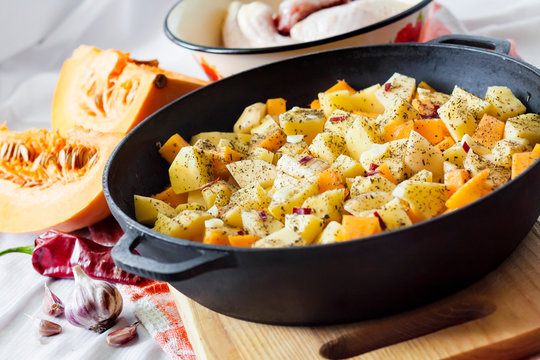 Cooking one-pot meal - chicken thighs and legs with potatoes and pumpkin