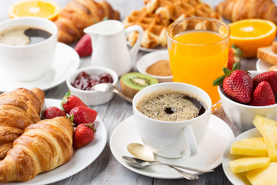 Continental breakfast table with coffee, orange juice, croissants