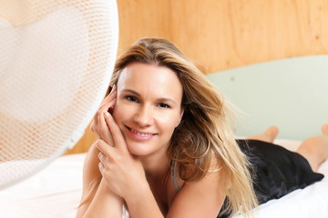 Hübsche Frau vor Ventilator Sommerhitze