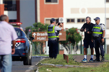 Brazil's Economy Minister Paulo Guedes takes a picture with police officers as he walks during a physical exercise near his hotel in Brasilia