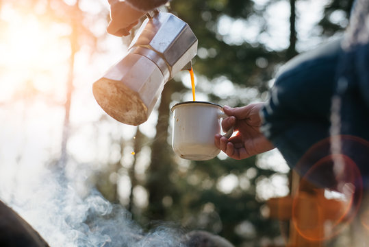 Horizontal outdoors image of young woman pours itself hot beverage in mountains near to bonfire . Girl sitting and holding a mug of coffee after hiking. Travel and healthy lifestyle concept