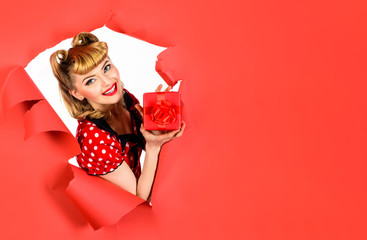 Woman with present looking through hole. Happy girl with gift breaking paper. Smiling retro woman hold gift box through hole in paper. Beautiful blonde woman in polka-dot dress. Pin up girl. Gift box.