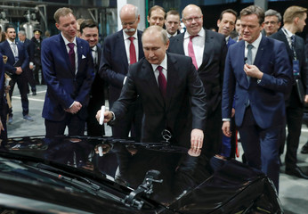 Russian President Vladimir Putin signs a car hood during the opening ceremony of a Mercedes Benz automobile assembly plant outside Moscow