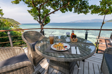 Ham sandwich with vegetables, french-fries and ice coffee on wooden table at patio of sea view