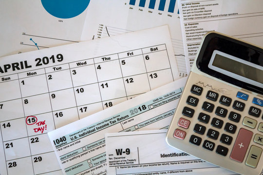 Top view of calculator, tax forms, graphs and calendar sheet with tax date marked