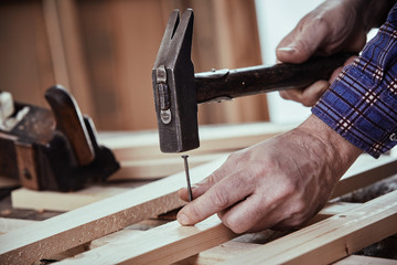 Carpenter hammering in a nail with vintage hammer