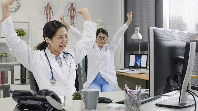 female asian doctors wearing lab coat sitting in clinic office working on computer read a good news look happy raising fist up. cheerful nurses coworker laughing about successful of patient surgery