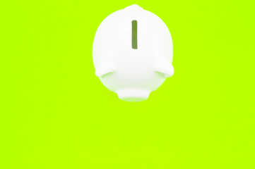 piggy bank on a lime green background - money saving and finance concept