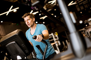 Man doing exercise on elliptical cross trainer in sport fitness gym club