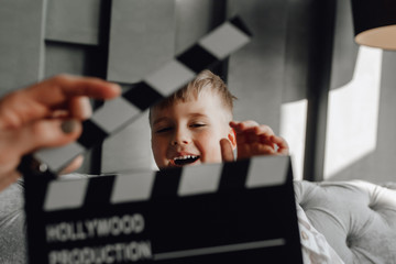 Cinema Clapper Board in Hand Blond Boy on Couch