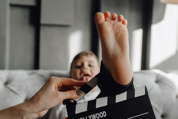 Caucasian Funny Boy Play with Cinema Clapper Board